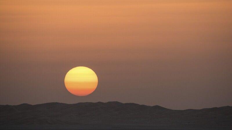 Orangerot verschwindet der Sonnenball hinter den Dünenhängen. © Diamir